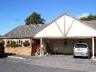 picture of a new build bungalow with car port